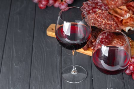 Photo for Wineglass with red wine and meat cuts board close up - Royalty Free Image
