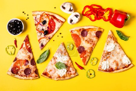 Selection of Assorted pieces pizza on yellow backg...