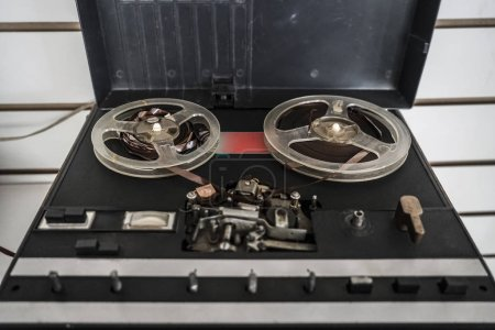 Old reel tape recorder, standing on wooden table, retro style