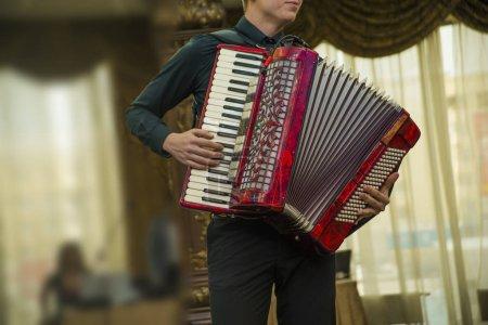 Man playing  red modern accordion. no face.
