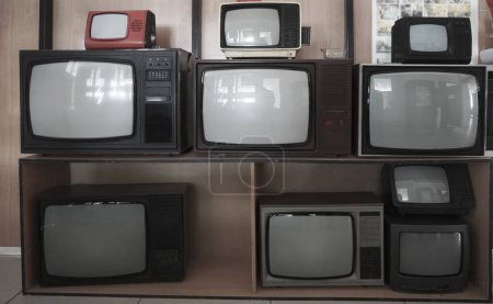 shelf near wooden wall with many vintage, aged, used  TV - television receivers