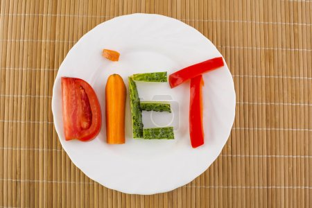 white plate with laid out  word - diet - composed of slices of different vegetables