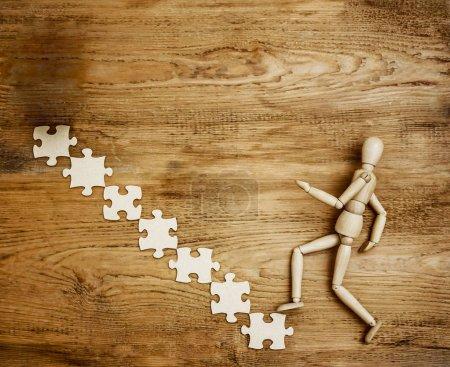 Photo pour Mannequin grimpant l'échelle de puzzles sur un fond en bois. carrière. les affaires. finances . - image libre de droit