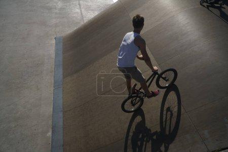 Foto de Deporte de verano. Joven mostrando truco de estilo libre con su bicicleta extrema bmx. Joven ciclista en zona de hormigón. día soleado y sombra - Imagen libre de derechos