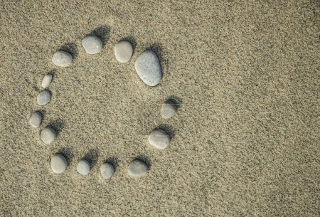 gray pebble stones on a sand beach background. empty round frame.