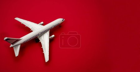 Photo for Metal  plastic toy - airplane s on red paper background. modern passenger plane isolated on red paper backdrop - Royalty Free Image