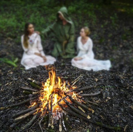 Photo for Two beautiful witches looking at the fire in dark forest. magician .  focus on fire - Royalty Free Image
