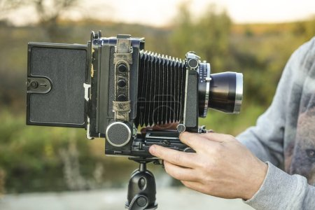 man with  vintage historical photo Camera on outdoor background.