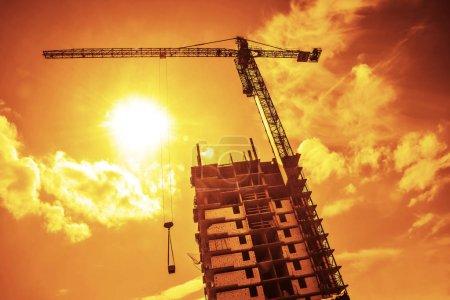 Photo pour Silhouette bâtiment grue et bâtiment om soir ciel toile de fond - image libre de droit