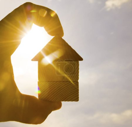 male hand holding  wooden house toy against sunny sky with sun rays