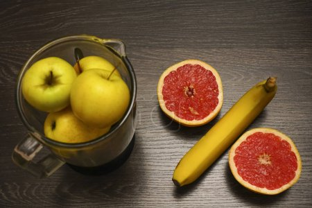 Photo for Percent sign, symbol, concept made from two grapefruit halves  and banana. black wooden background. - Royalty Free Image