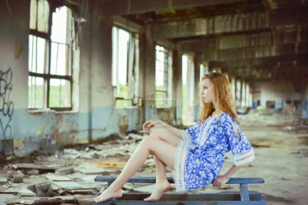 Photo for A portrait of a young miserable crying girl sitting on blue wooden table in abandoned interior. Concept of loneliness. Only friend. - Royalty Free Image