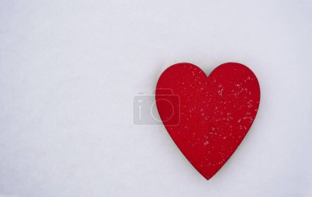 Photo for Red wooden heart on  white artificial snow with snowflakes - Royalty Free Image