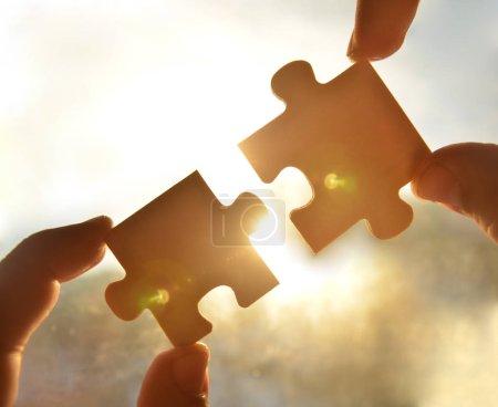 Zeiger mit Puzzleteilen mit Sonnenuntergang Hintergrund.