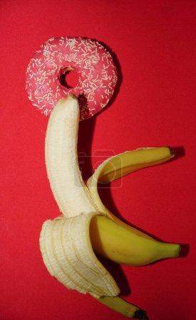 Photo pour Bouée rouge et récolter jaune banane isolé sur fond rouge. idée de sexe. - image libre de droit