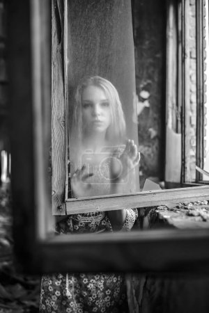 Young adult woman by dirty window....