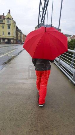Foto de Vista trasera de la mujer con paraguas rojo caminando por el casco antiguo . - Imagen libre de derechos