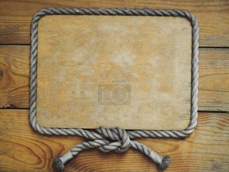 Foto de Primer plano de un letrero de madera vacío con cuerda alrededor en el fondo de tablas de madera - Imagen libre de derechos