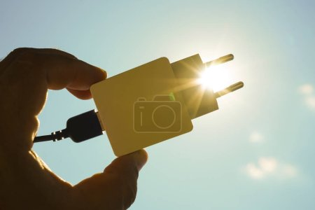 Photo for Sun energy with plug (Power Supply) connection ready to get power. silhouette of power socket against sun rays - Royalty Free Image