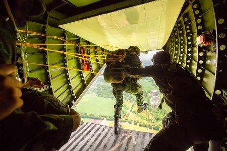 Photo pour Rangers parachutés d'avions militaires, Soldats parachutés de l'avion, soldat aéroporté isolé, pratique du parachutisme, parachutistes sautant d'un avion . - image libre de droit