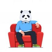 Man with panda bear head sitting in armchair