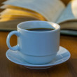 Cup of coffee and book on wooden table...