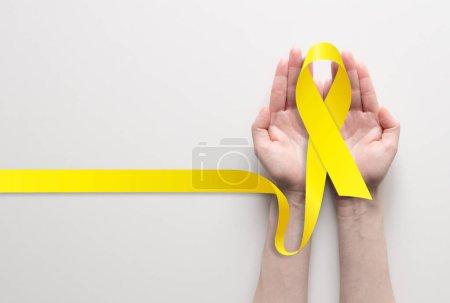 Photo pour Holding ruban jaune, symbole de sensibilisation au cancer, soutien médical et prévention avec l'aide de deux mains. Place pour le texte. - image libre de droit