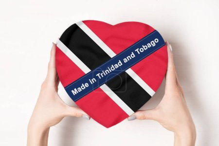 Inscription Made in Trinidad and Tobago the flag of Trinidad and Tobago. Female hands holding a heart shaped box. White background.