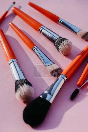 Photo pour Ensemble de pinceaux pour maquillage de couleur orange sur fond rose - image libre de droit