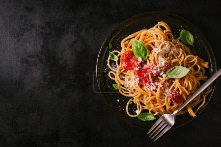 Photo pour Délicieuses pâtes italiennes classiques et appétissantes avec sauce tomate, parmesan au fromage et basilic sur une table noire. Vue d'en haut, horizontale - image libre de droit