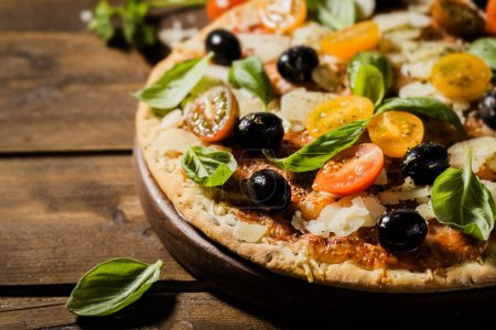 Photo for Top view of tasty appetizing classic italian traditional pizza with cheese, olives, basil and fresh vegetables on wooden table. - Royalty Free Image