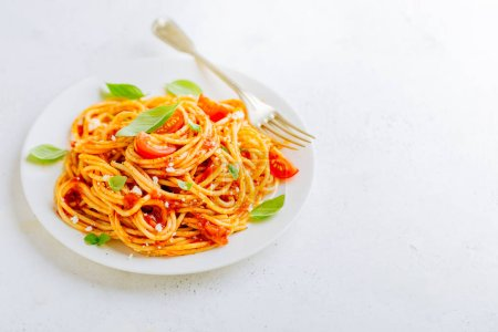 Photo for Appetizing italian pasta dish with tomato sauce on plate on white table. Closeup - Royalty Free Image