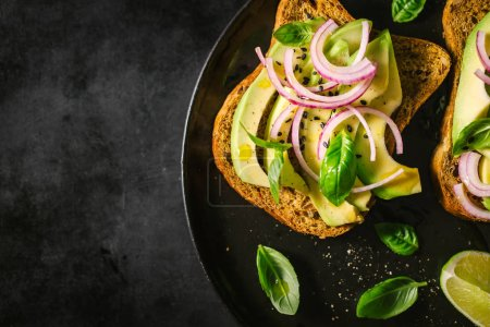 Photo for Fresh ready served avocado toasts with spices on dark table. Ready to eat. Closeup - Royalty Free Image