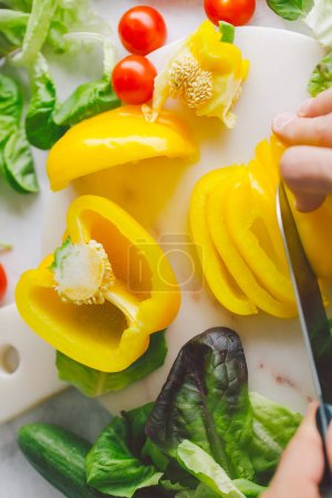 Photo for Man preparing cooking fresh detox healthy salad on table. Cutting yellow paprika. Closeup - Royalty Free Image