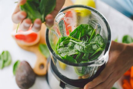 Photo for Man cooking healthy detox smoothie with fresh fruits and green spinach. Lifestyle detox concept - Royalty Free Image