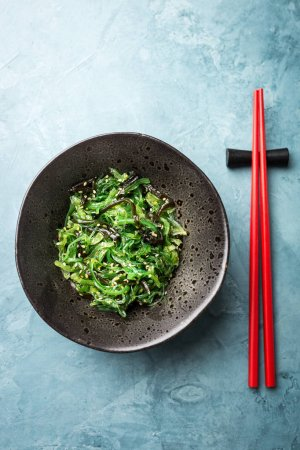 Photo for Tasty appetizing seaweed salad on plate on table. Top View with Copy Space - Royalty Free Image