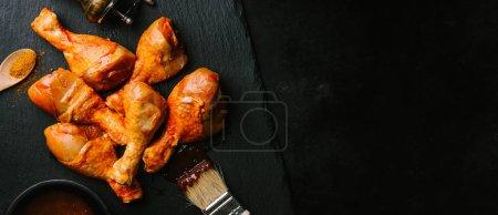 Preparing raw chicken barbecue legs on table. Closeup.