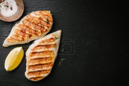 Photo pour Blanc de poulet cuit au four savoureux appétissant grillé servi sur fond d'ardoise noir. Vue d'en haut avec espace copie - image libre de droit