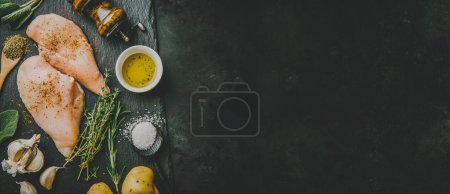 Photo for Raw chicken breast with ingredients ready for cook on dark black table. Horizontal with copy space. Cooking healthy food concept - Royalty Free Image