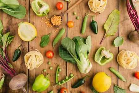 Photo pour Concept d'alimentation saine et propre. Légumes frais entiers et coupés sur table en bois. Pose plate . - image libre de droit
