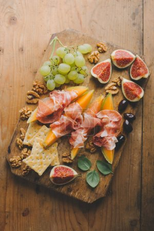 Photo for Tasty Spanish Mediterranean appetizers on old board on vintage wooden table. Top View - Royalty Free Image
