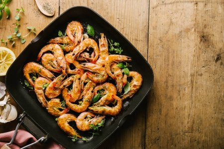 Photo for Tasty appetizing roasted shrimps prawns with spices on pan with ingredients on wooden table. Top View with Copy space. Food Background Italian Kitchen Concept - Royalty Free Image