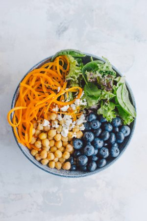 Photo for Buddha bowl salad with pumpkins, blackberries, chickpeas and spinach on white table. Healthy Clean eating Detox Concept. Top View with Copy Space - Royalty Free Image