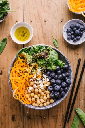 Photo for Ingredients for cooking Buddha bowl salad with pumpkins, blackberries, chickpeas and spinach on wooden table. Healthy Clean eating Detox Concept. Top View - Royalty Free Image
