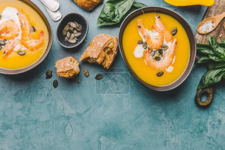 Photo for Autumn food - pumpkin soup with cream, shrimps and seeds in bowls on table. Served for dinner. View from above - Royalty Free Image