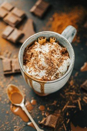 Photo pour Chocolat chaud avec des morceaux de chocolat et de crème en tasse sur tableau noir - image libre de droit