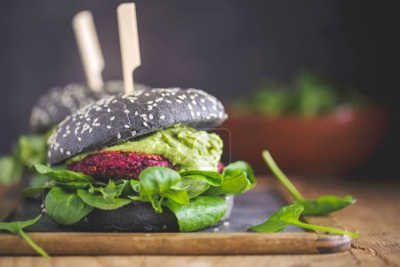Photo for Tasty appetizing healthy vegan black burgers with beetroot, quinoa and avocado sauce served on wooden table - Royalty Free Image