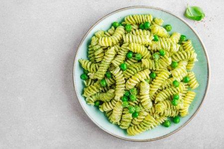 Photo pour Vue de dessus des pâtes italiennes al bronzo, sauce pesto, pois verts, basilic et fromage servi sur table gris - image libre de droit