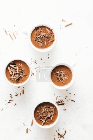 Photo for Top view of hot chocolate with chocolate chunks and cream in small cups served on white background - Royalty Free Image