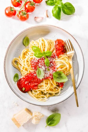 Photo for Top view of spaghetti with tomato sauce and parmesan in bowl - Royalty Free Image